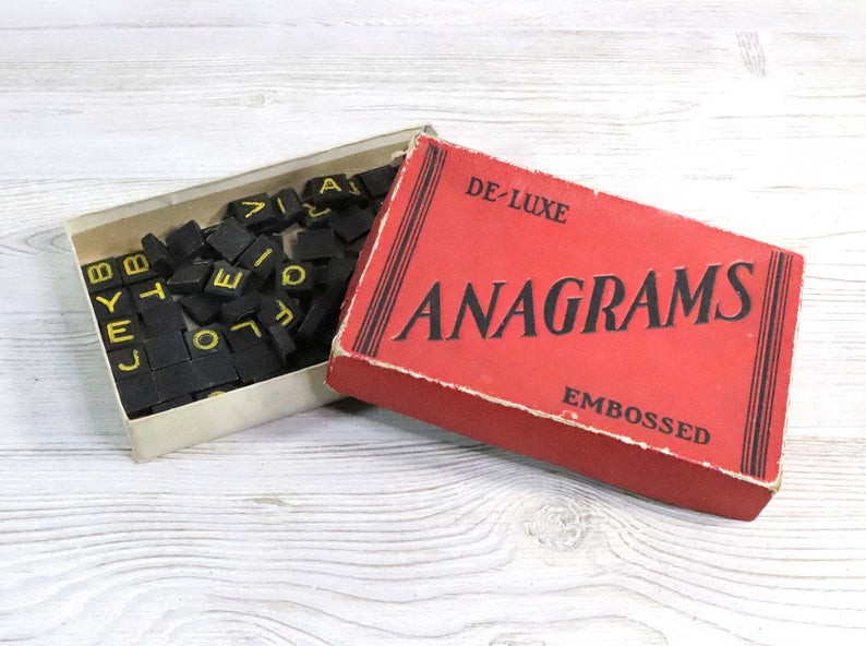 "an antique board game box labeled ""de-luxe anagrams"". the box is open showing scrabble-like tiles inside."