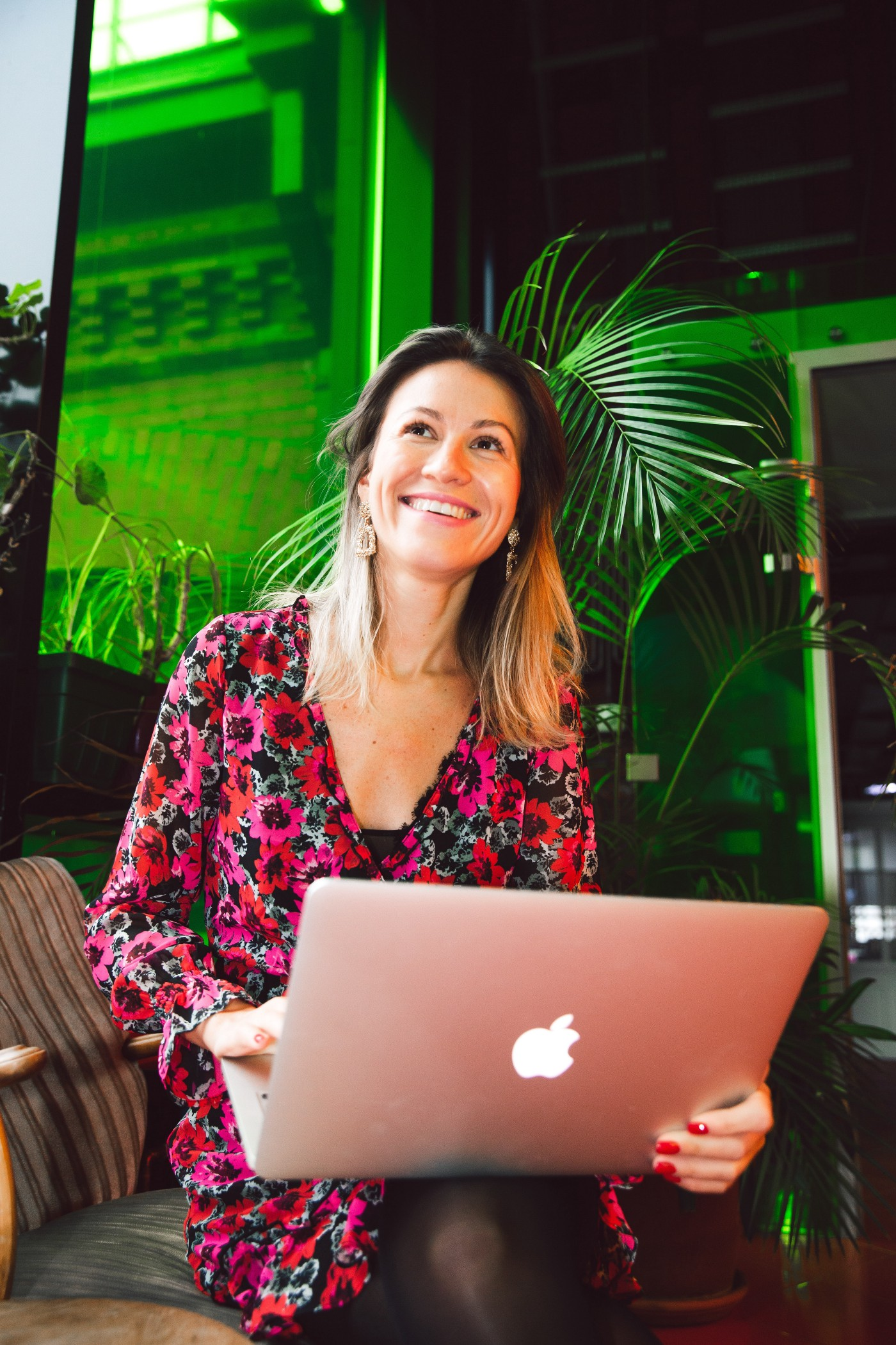 Smiling woman dressed in red, sitting behind her pink laptop. Background full of plants and is very green. (Freelancer)