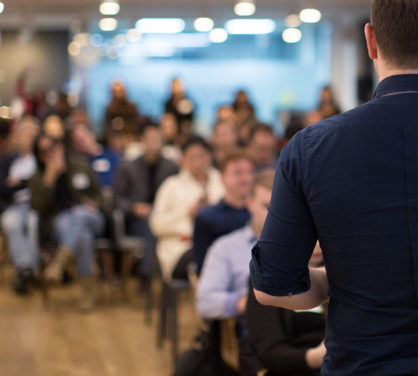 A man presenting to a room full of people.