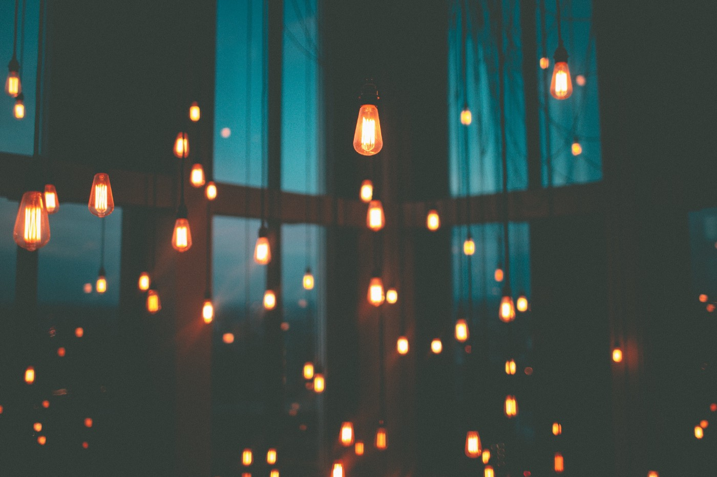 A picture of many hanging lightbulbs burning brightly against the backdrop of a dark room partially illuminated by light coming through blue curtains.