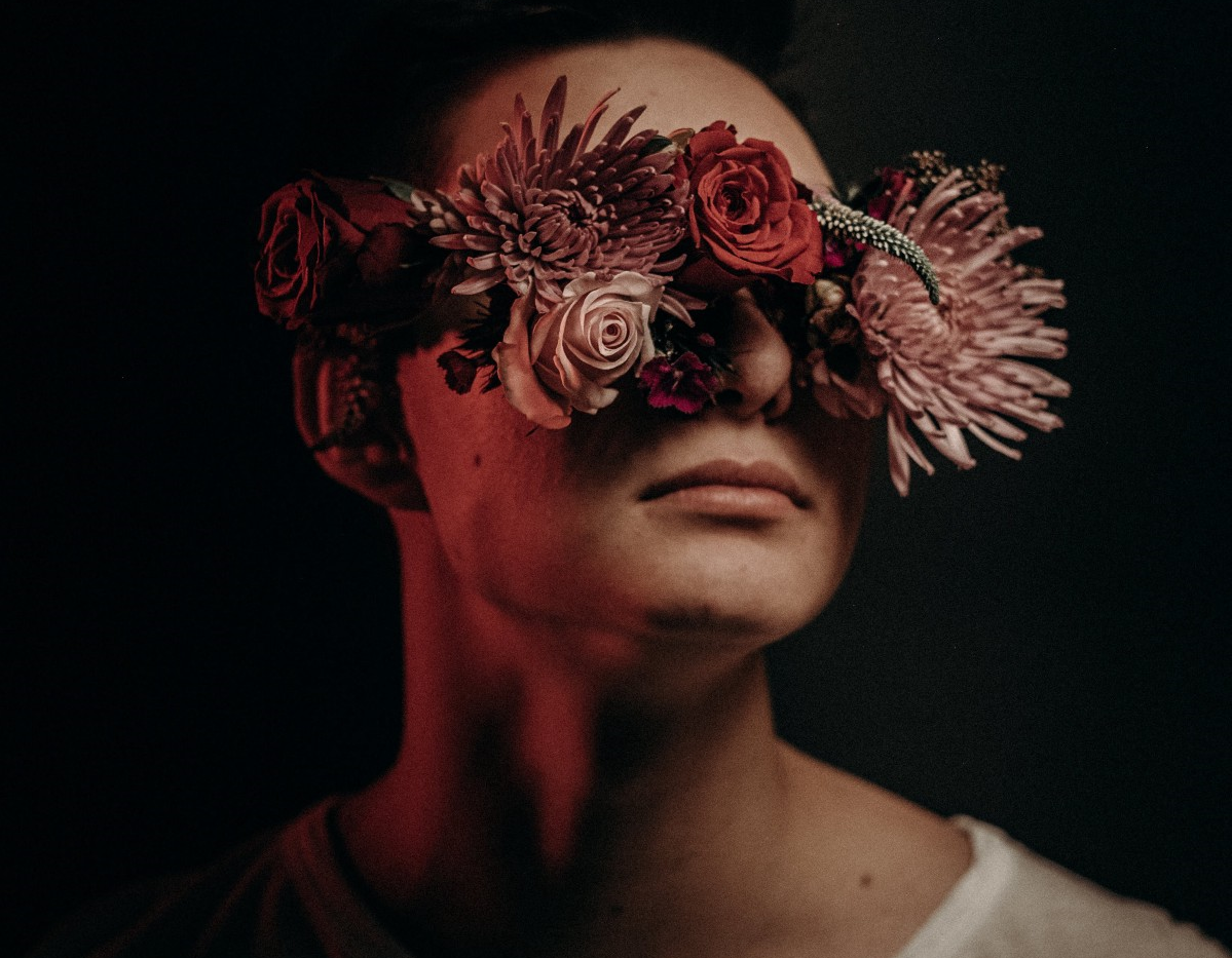 Photo of a man with his eyes covered by flowers.