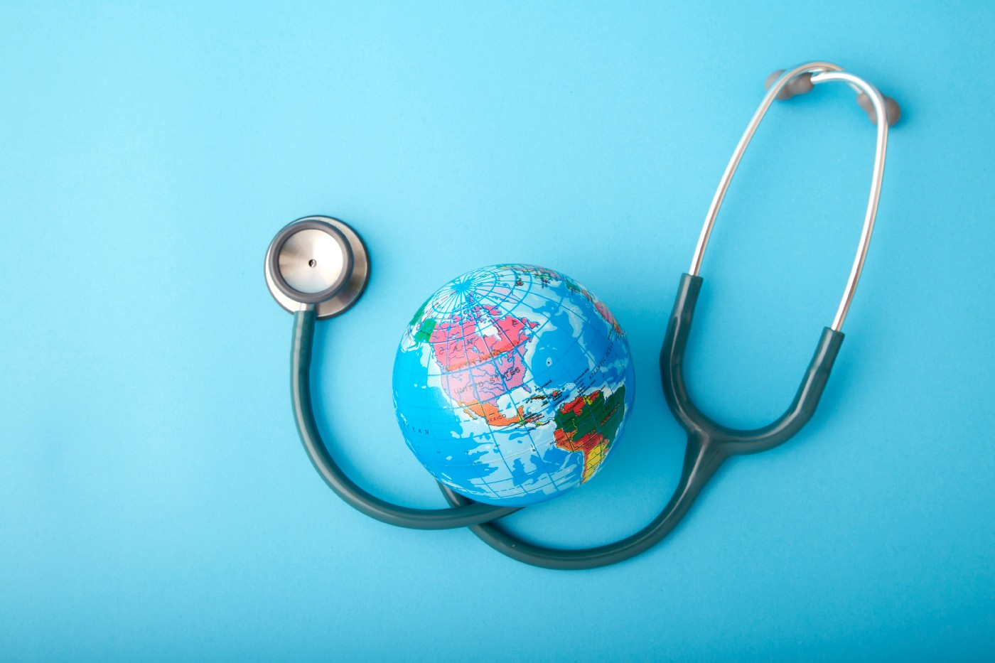 A close up of a stethoscope next to a small globe on a blue background.