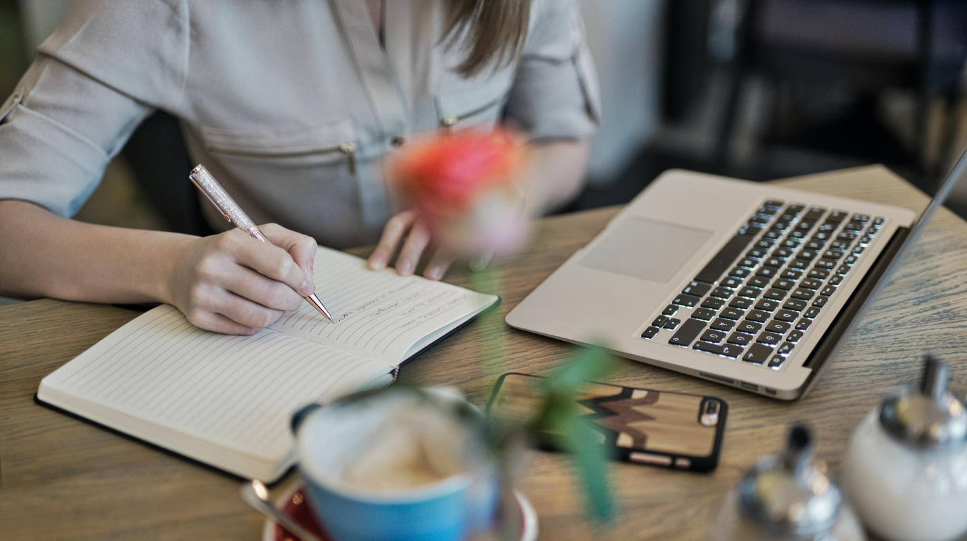 Woman in light denim shirt writes in a notebook at her laptop on a wooden table. A rose sits in the middle of the frame out of focus.