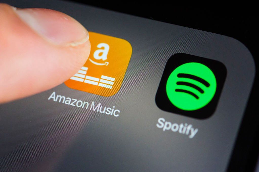 The app logos of Amazon Music and Spotify on the screen of a smartphone.