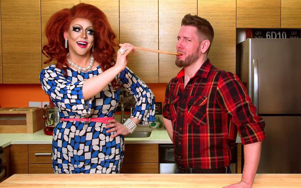 Drag queen Honey LaBronx in a patterned dress, holding a wooden spoon to someone's mouth, both standing in a kitchen.