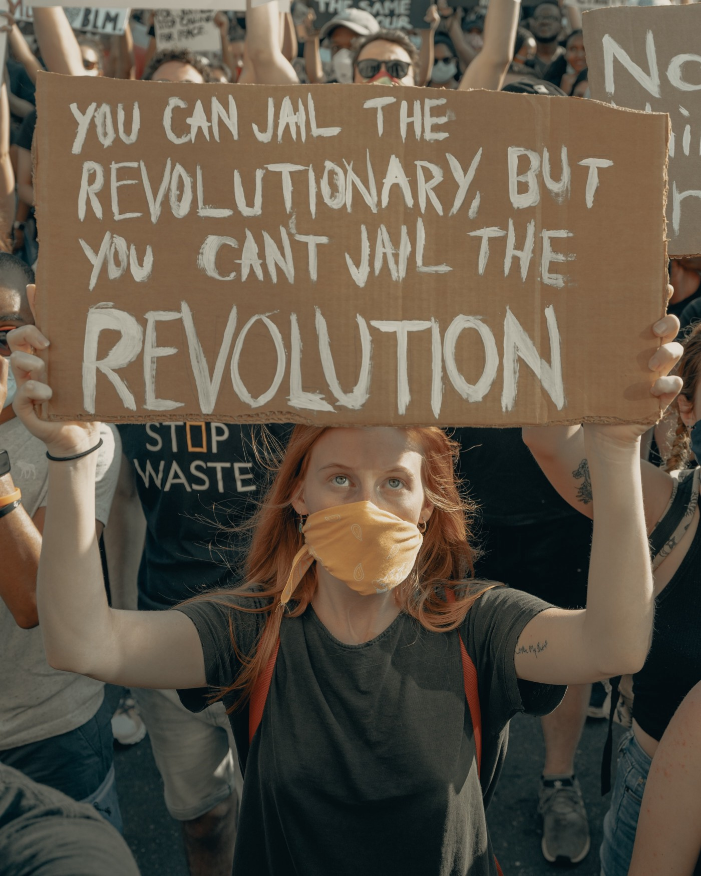 """Photo of a young woman in a crowd of protesters marching together. She is wearing a COVID mask and holding up a cardboard sign with the hand painted message, """"YOU CAN JAIL THE REVOLUTIONARY, BUT YOU CAN'T JAIL THE REVOLUTION"""""""