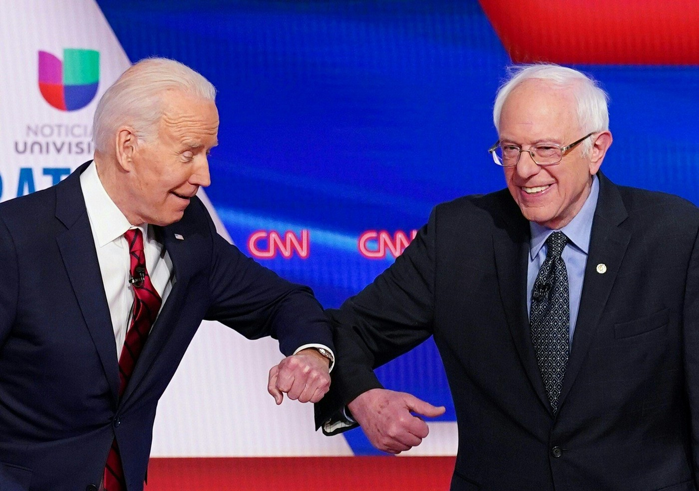 A photo of Joe Biden and Bernie Sanders elbow bumping each other at the 11th Democratic Party 2020 presidential debate.