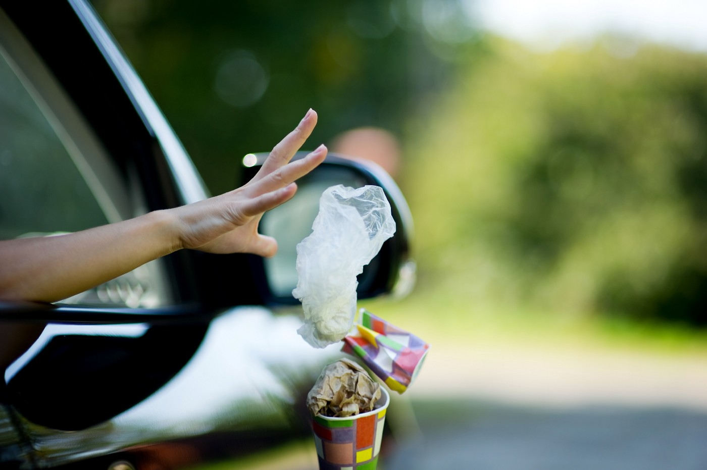 A person tosses a handful of colourful takeout garbage from a front car window.