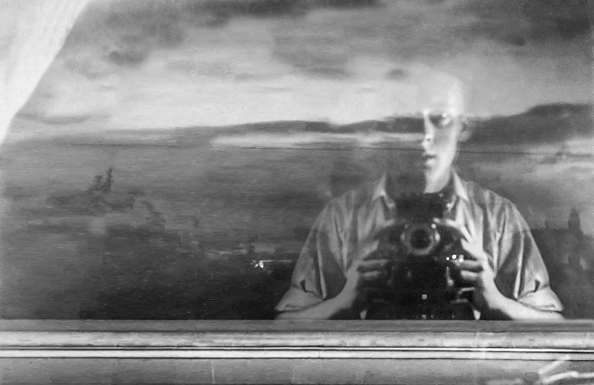 A 1947 black and white self-portrait of a young man, holding a camera, taking his own picture, his face reflected in a window with a cloudy sky beyond
