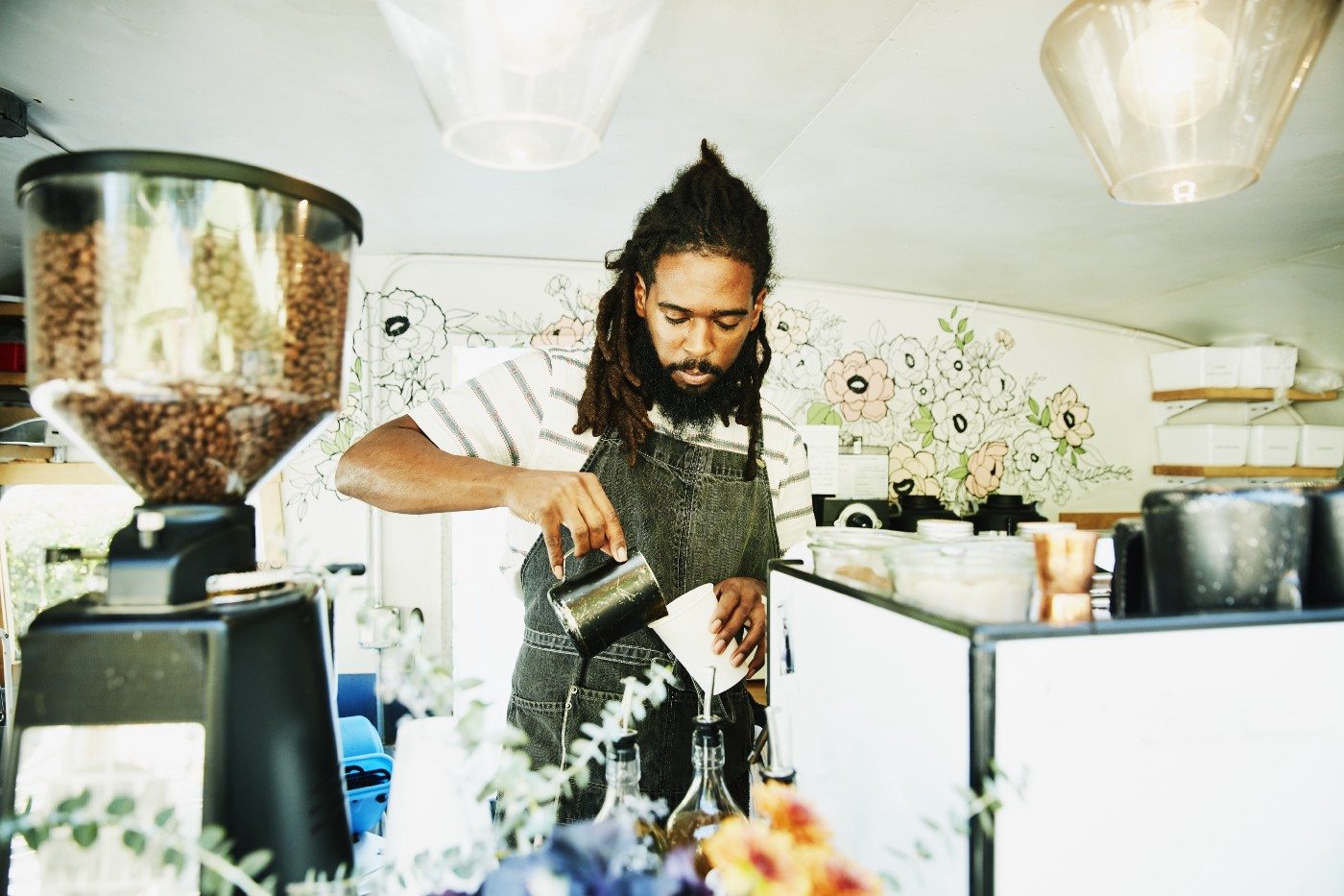 A Black barista, their long locs tied back, pours milk into a coffee cup behind the counter of a coffee truck.