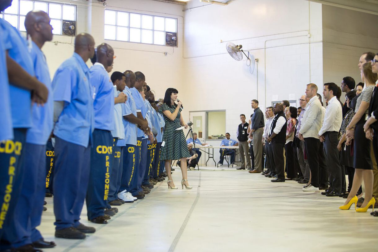 A line of prisoners (mostly black) face a line of prison staff (mostly white) whilst a women with a microphone walks between