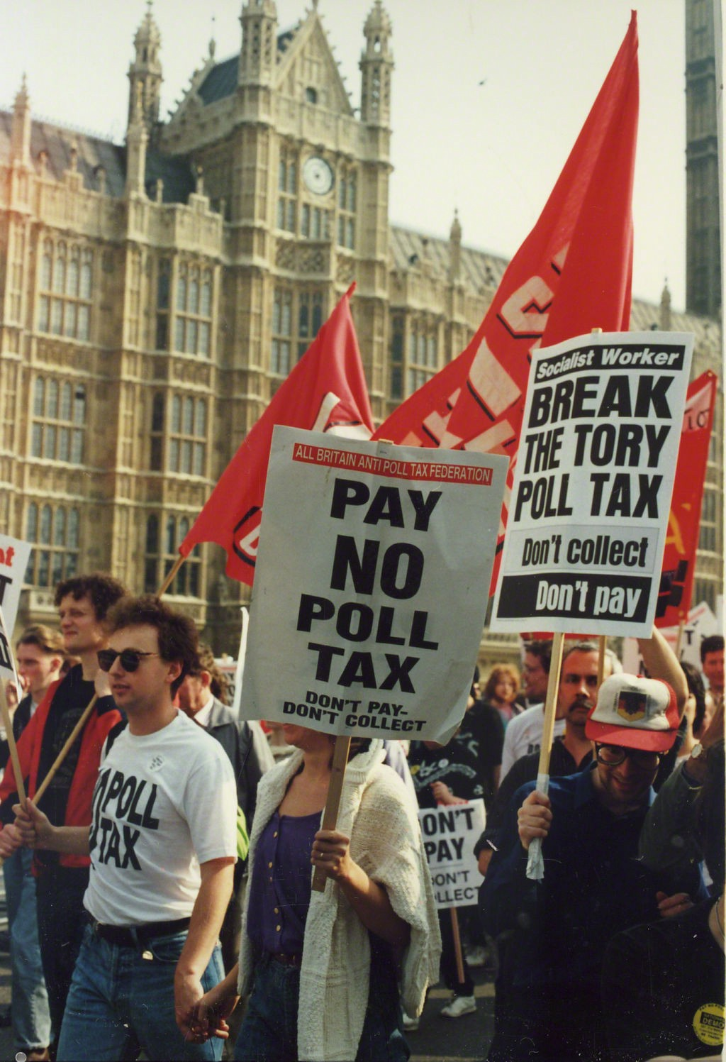 A group of protestors walk past one of the old buildings of London, holding placards and banners against the Poll Tax.