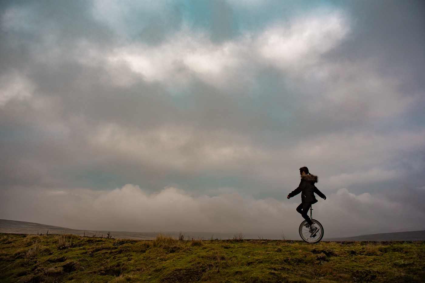 girl unicycling on moors with moody sky as backdrop