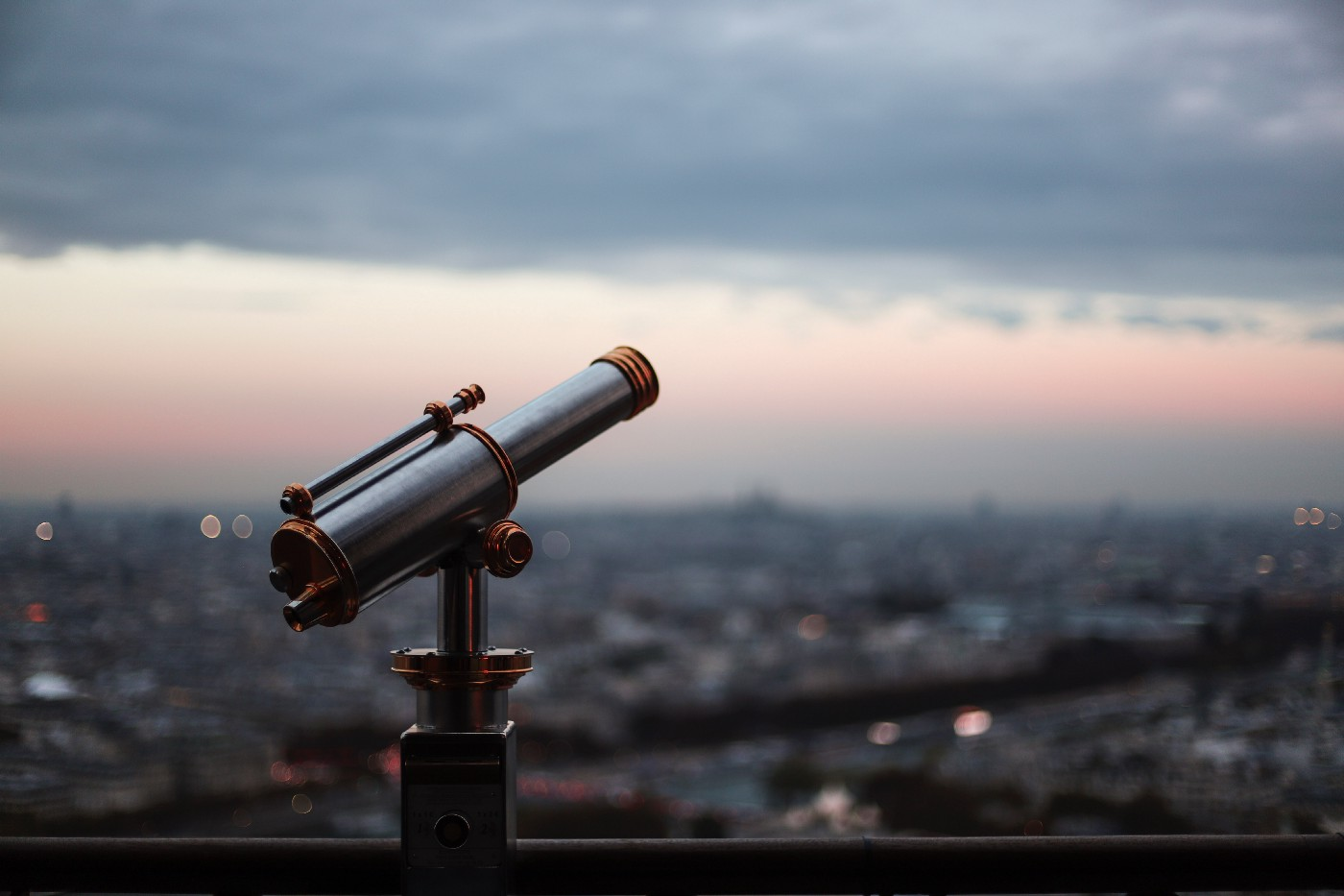 Telescope pointing out over a cityscape with a beautiful pink tinge of sky