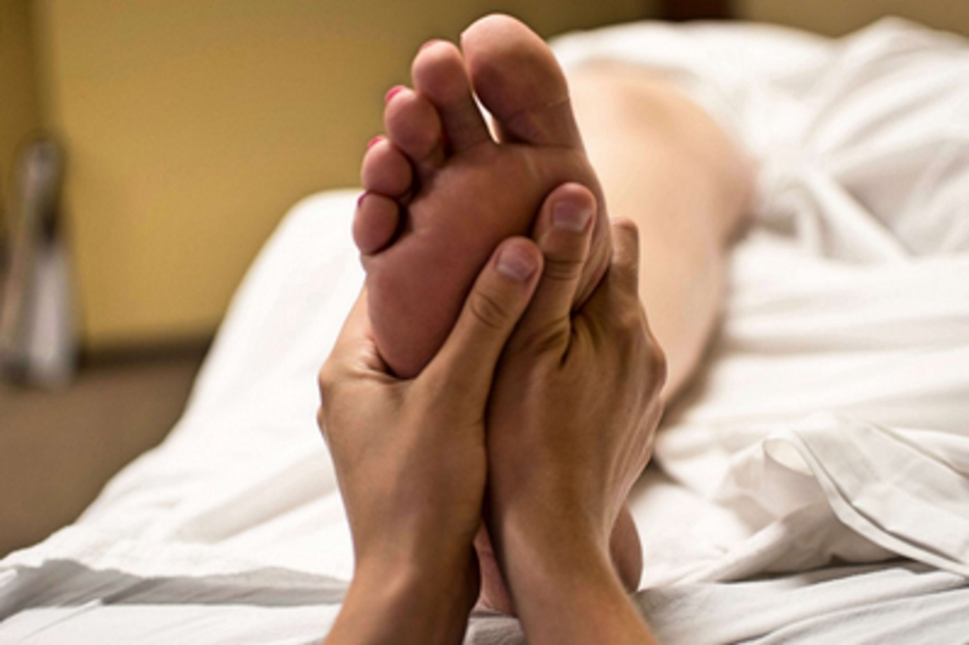 Photograph of foot with hands giving massage