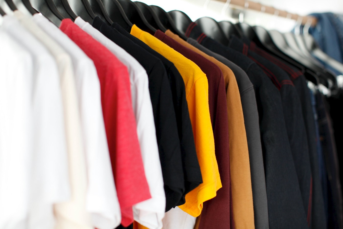 Different colour T-shirts on hangers