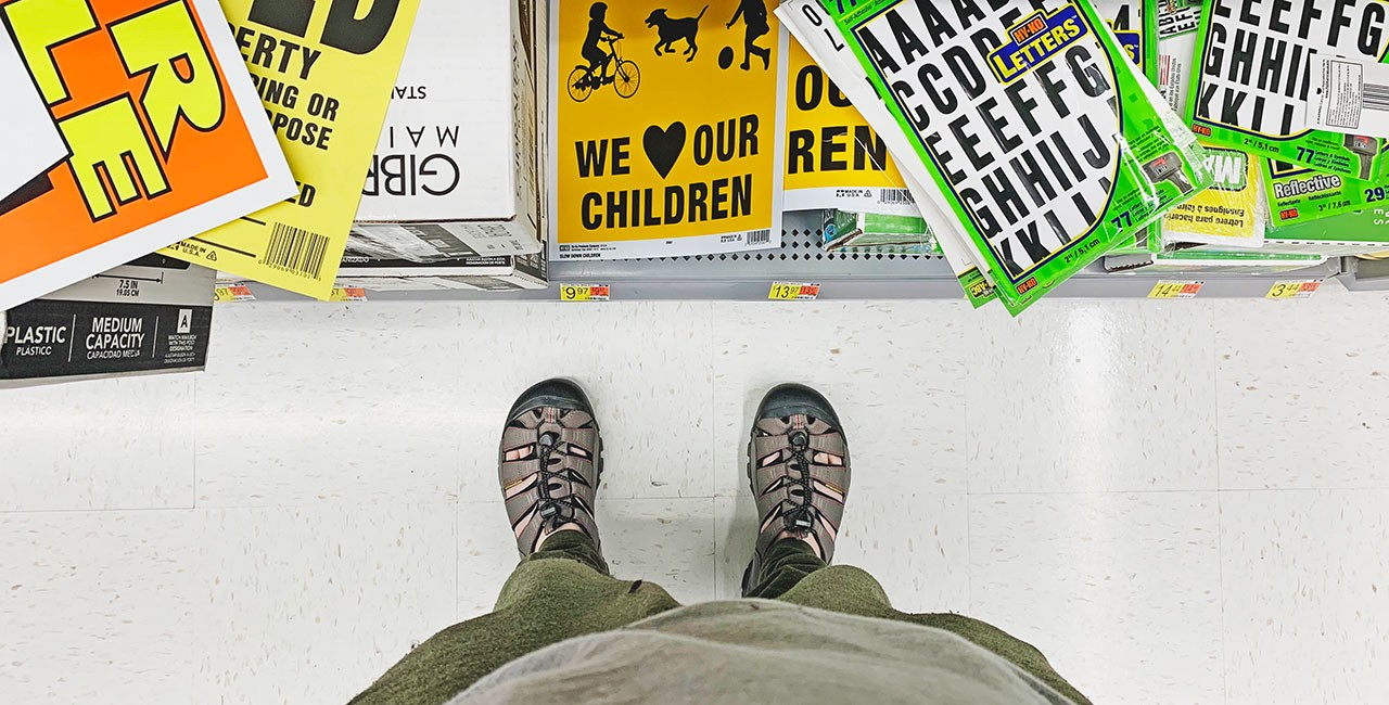 View of a man's lower body seen from above, clad in a disheveled T-shirt, sweatpants, and wading shoes, standing before a floor bin of adhesive letters and yard signs at a Walmart store