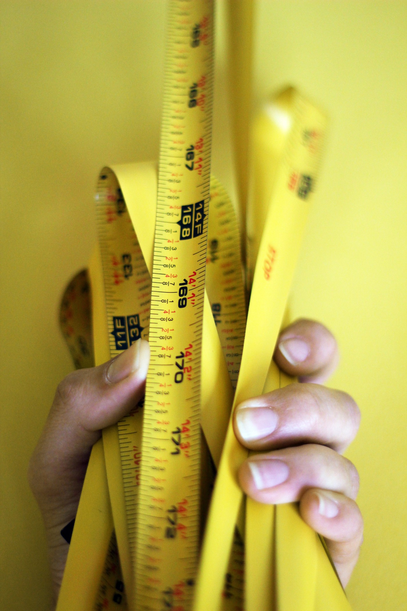 A hand holding a bunched up tape measure together. The 14 Foot marker is visible in the foreground, with several bunches of previous measurements behind it.