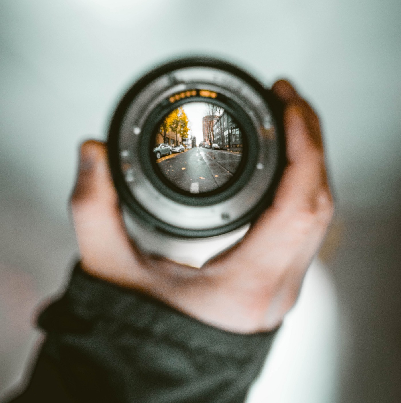 A hand holds up a lens that brings the surrounding street and cityscape into focus.