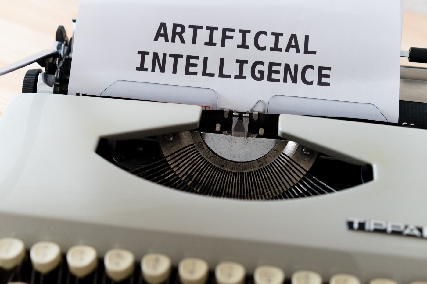 "An antique typewriter with a sheet of paper in it that says ""Artificial Intelligence"""