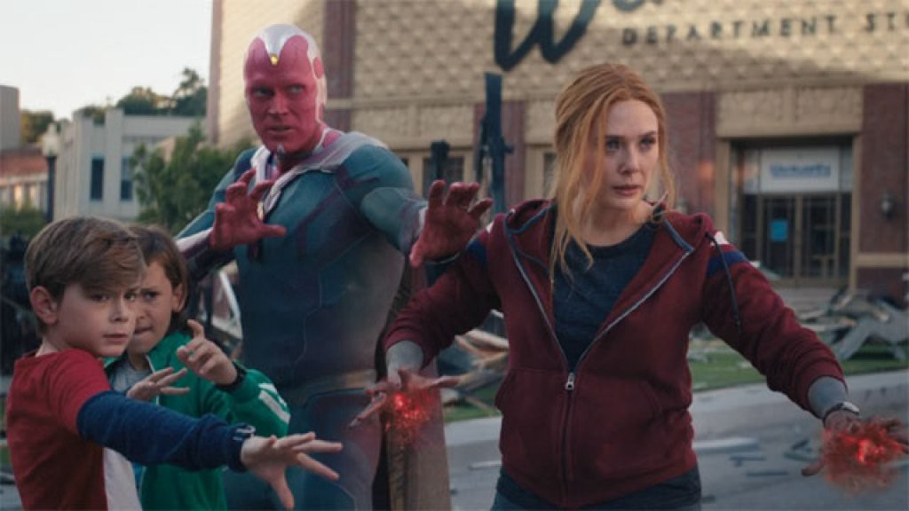 Two boys, Vision, and Wanda raising their arms in a stance to looking straight at SWORD agents offscreen