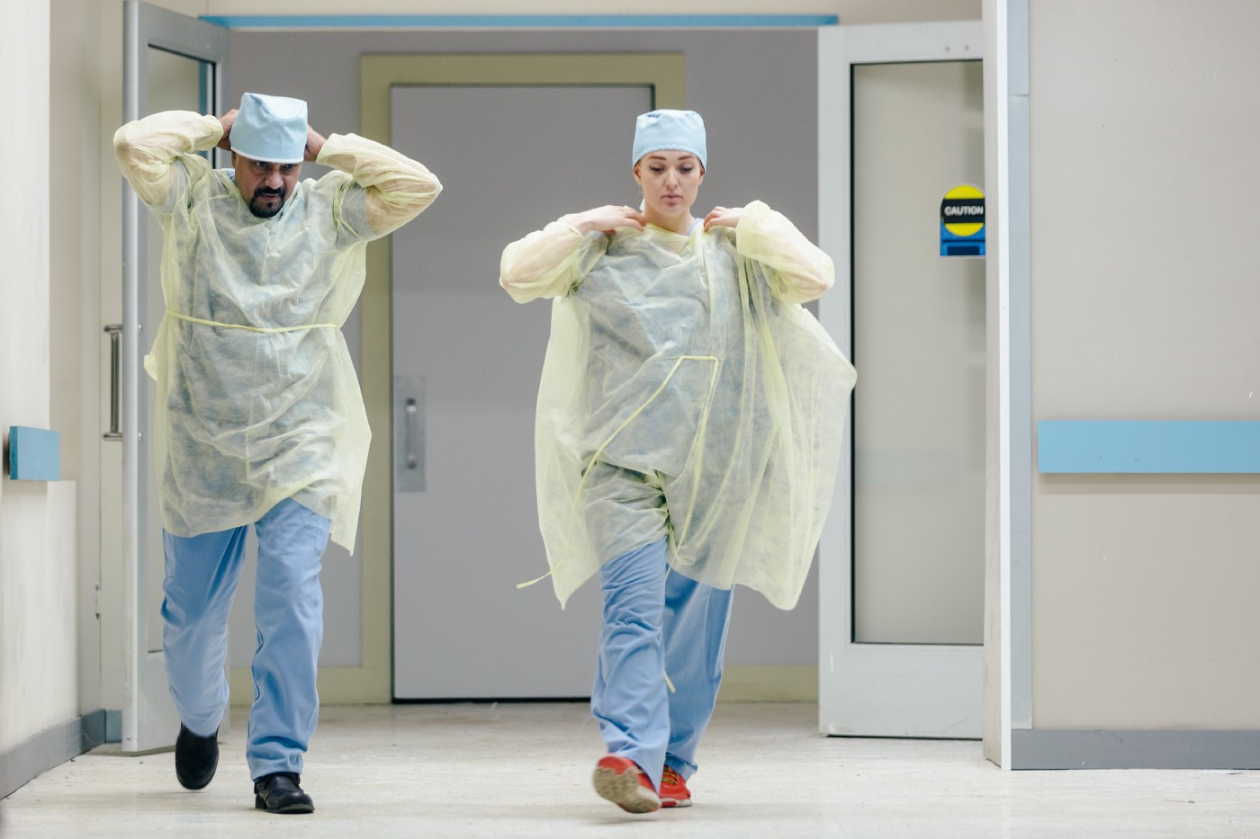 Two doctors put on PPE to care for patient