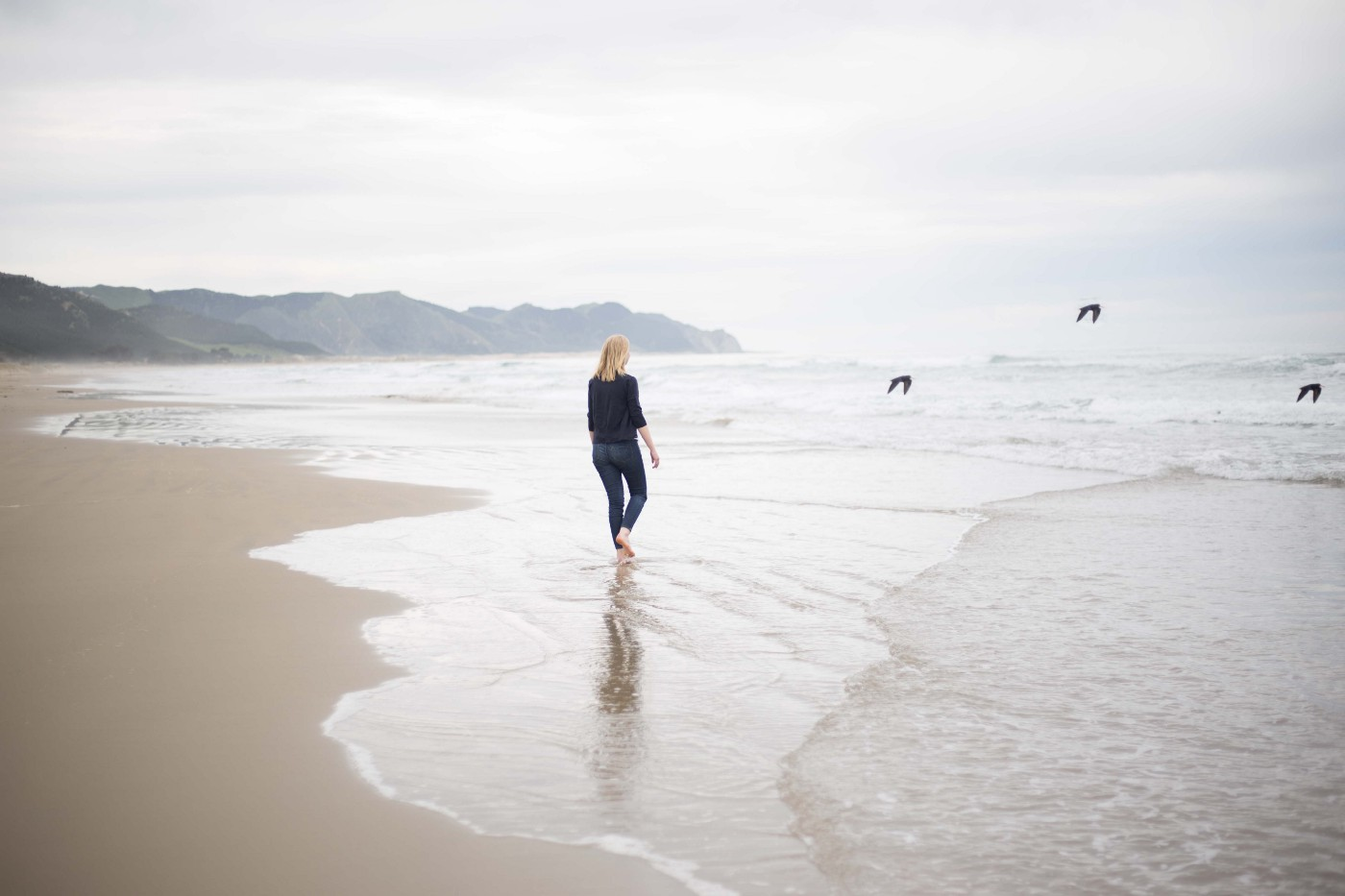 A young woman walking on the beach, and watching birds flying away