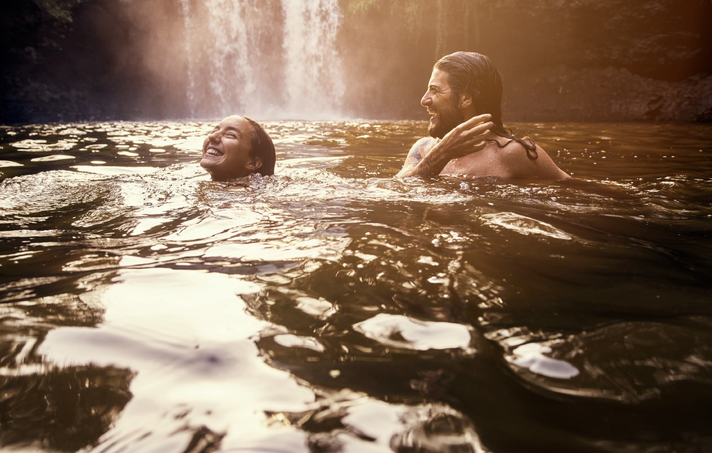 Couple bathing in a scene body of water with a waterfall behind them.