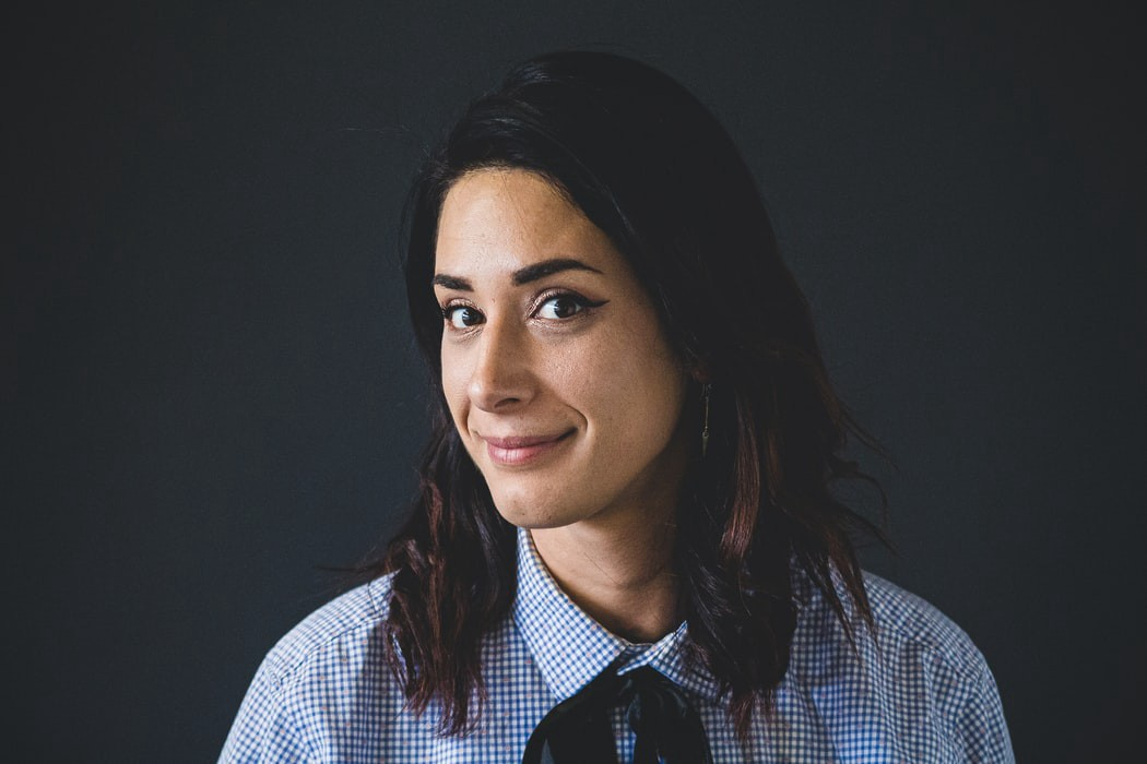 A smiling brunette in a checked shirt with a bow