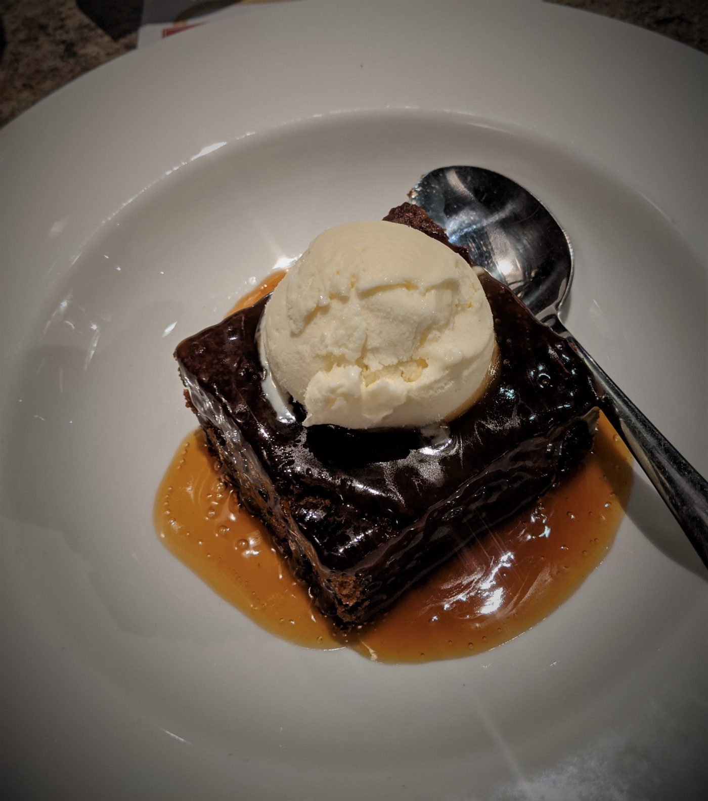 Sticky toffee pudding in white bowl topped with a scoop of ice cream