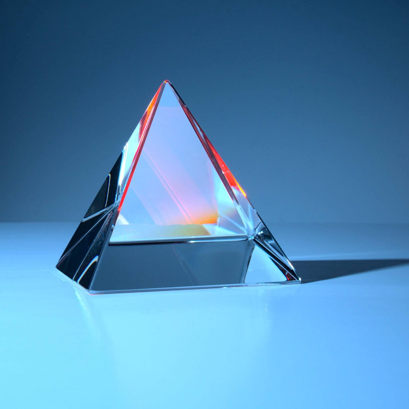 Crystall pyramid with reflections on a blue background