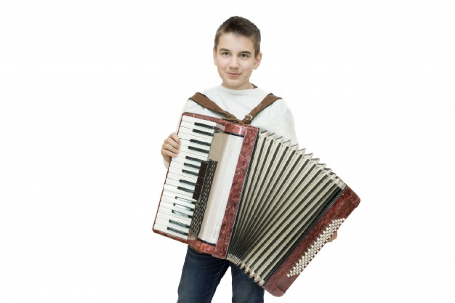 Eleven year old boy with brown hair, weating white t-shirt, standing while holding an accordion.