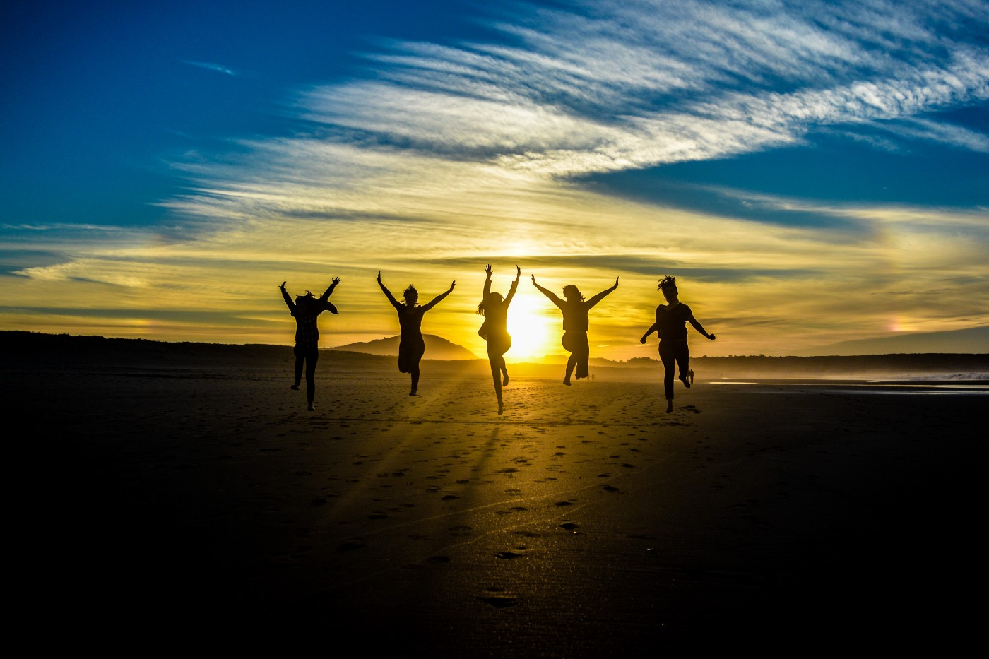 A group of people running on sand towards a sunset, leaping into the air