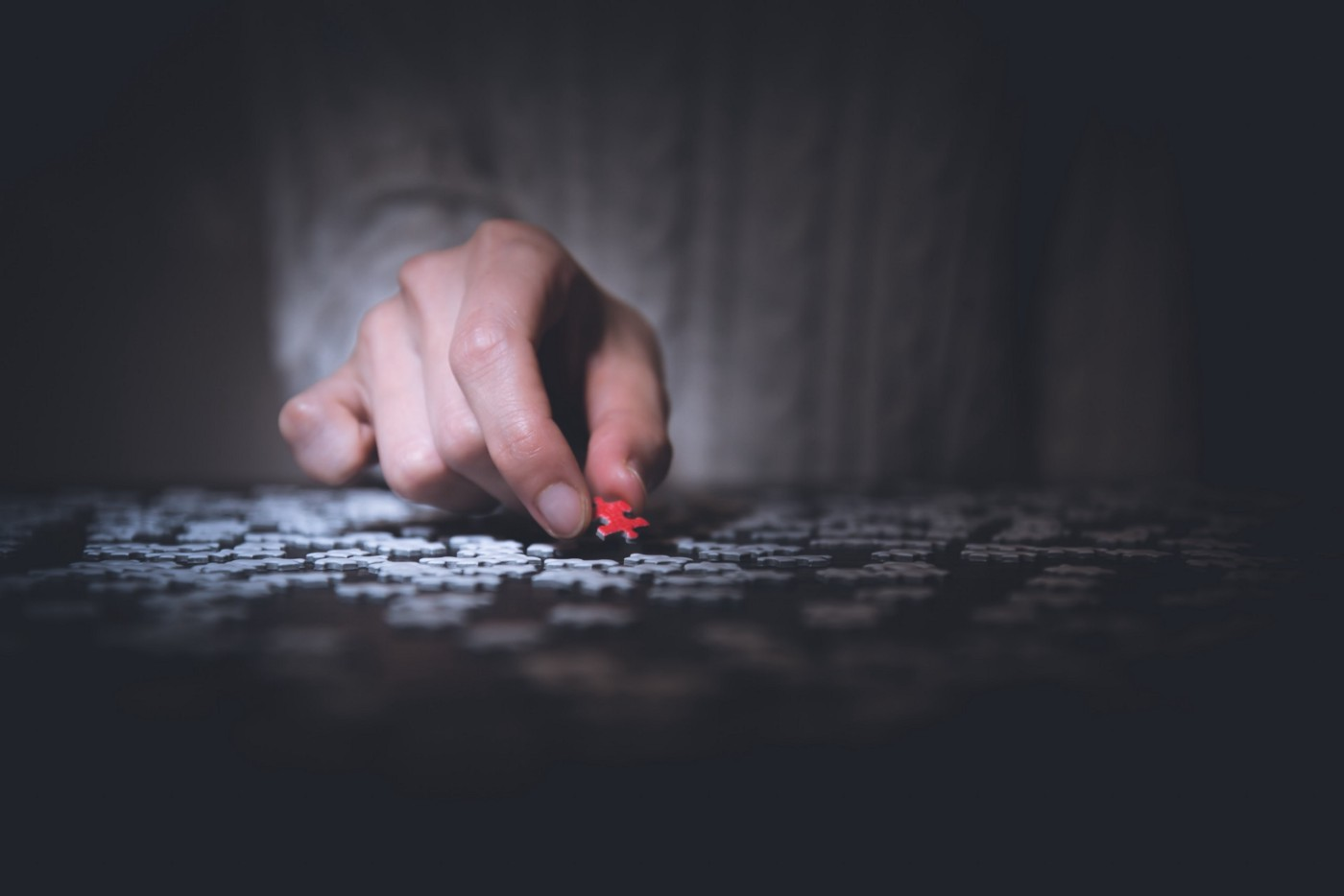 A hand picking one single piece of puzzle from a table full with lots of puzzle pieces.