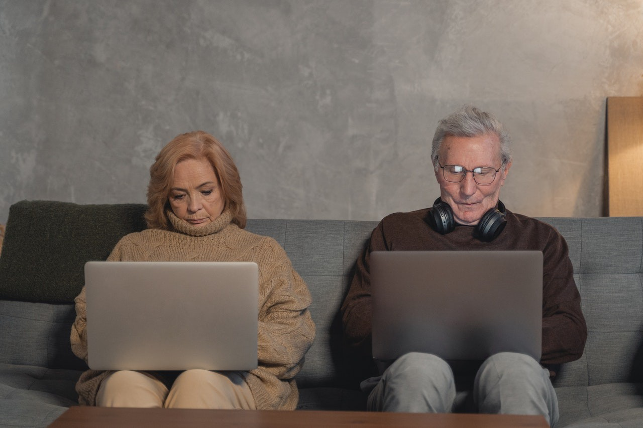 older man and woman sitting on a couch working on their laptops