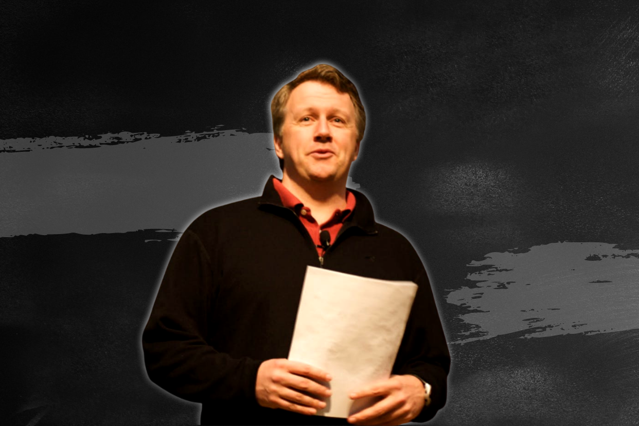 Paul Graham standing straight in front of the camera and holding a document.