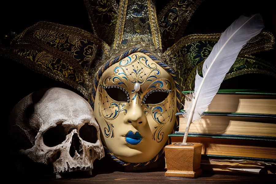 Still life of a desktop with an ornate volto-style masquerade mask, a human skull, a pile of old books, and a quill pen in a square ink pot.