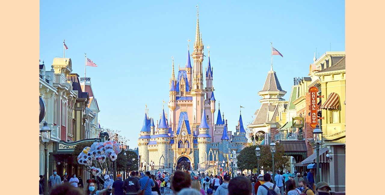 A fairy tale castle towers above the crowds at the end of a theme park midway in the style of an early 20th century American city