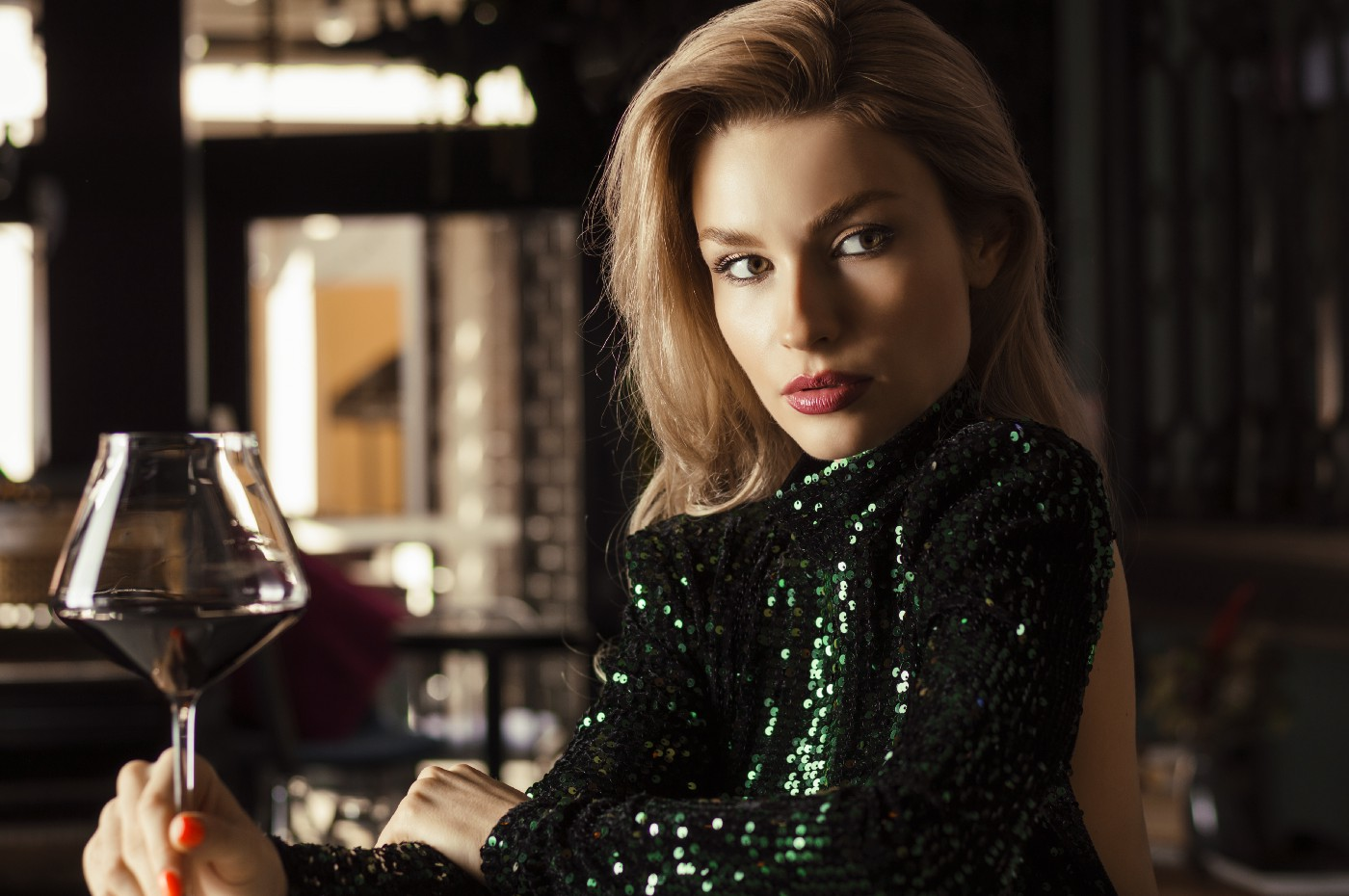 Attractive woman staring seductively while holding a glass of wine.