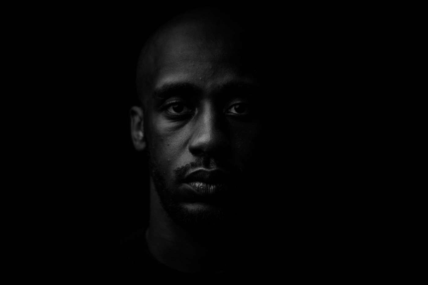 Close-up portrait of a young Black man against a black background.