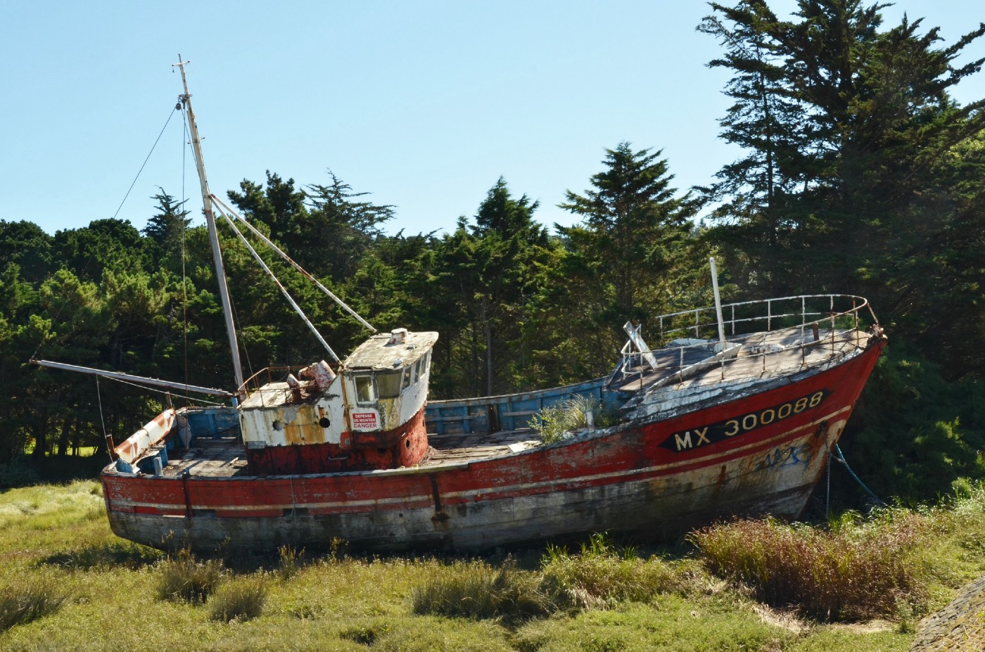 Old rusty ship on a dry land (on a grass field and some trees are behind). A neglected ship.