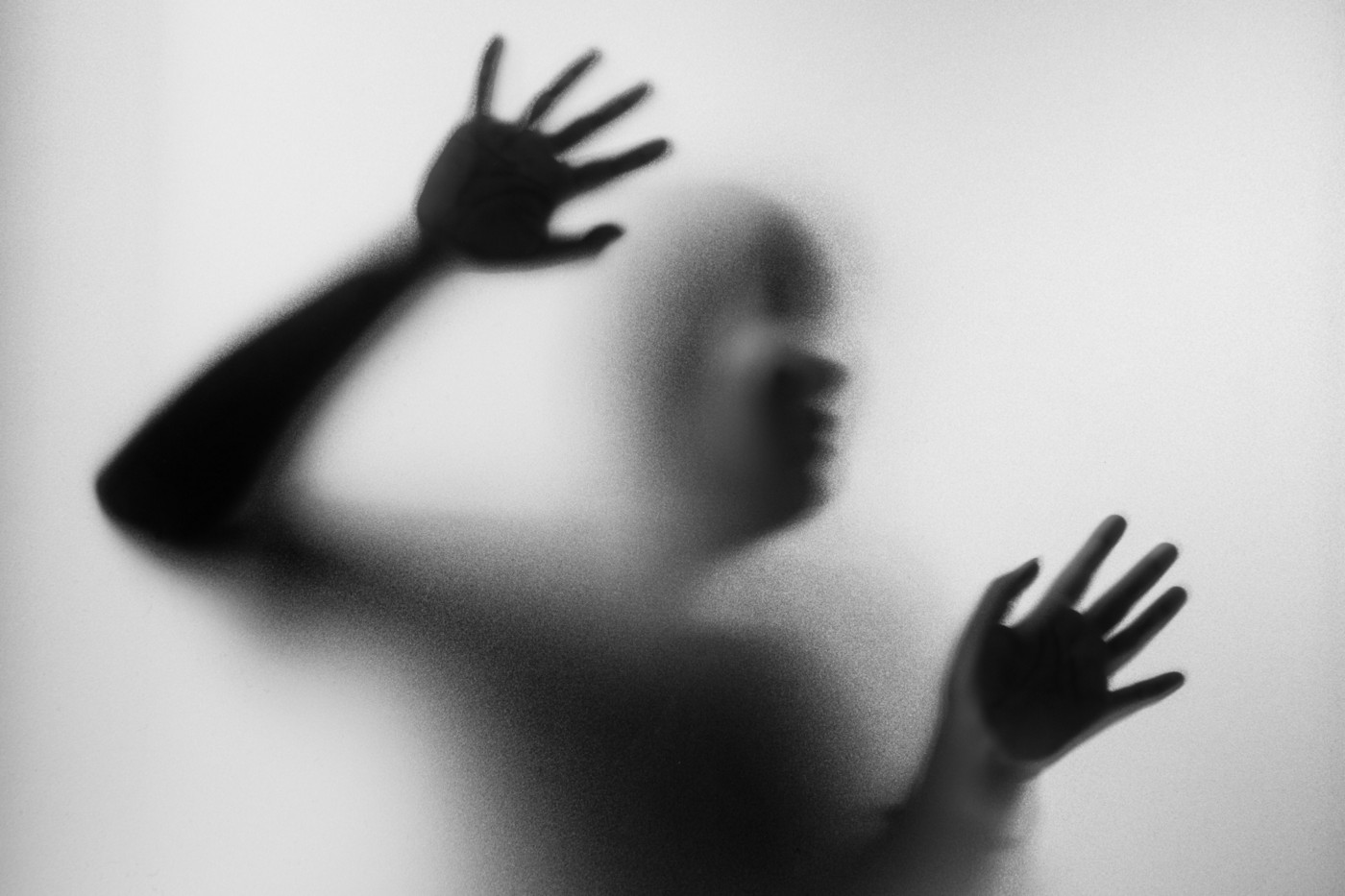 An eerie image of the silhouette of a person seen through frosted glass.