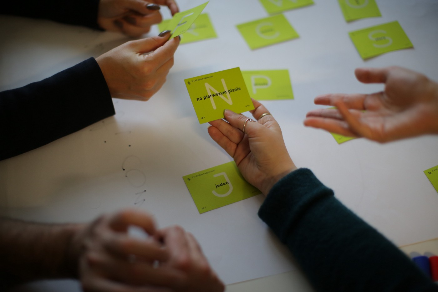 A group of people holding green cards with adjectives describing the differentiators for the solution they design.