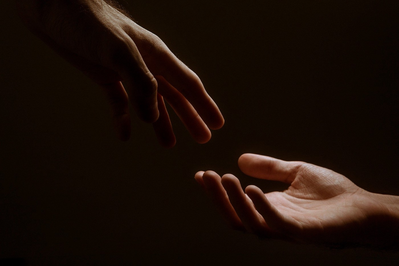 two hands reaching toward one another
