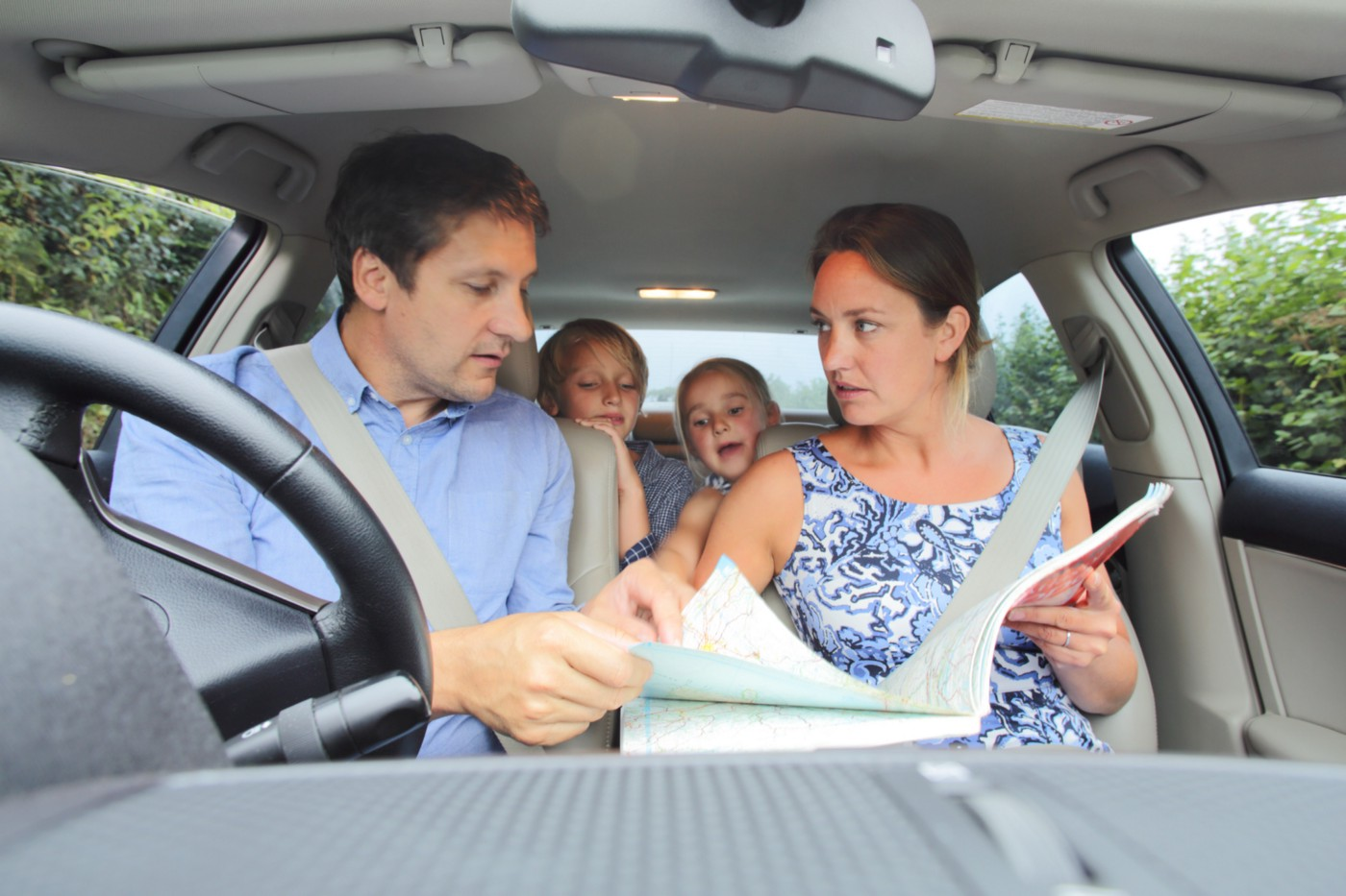 2 parents fight over map directions in the car while their children peer over the back seat.
