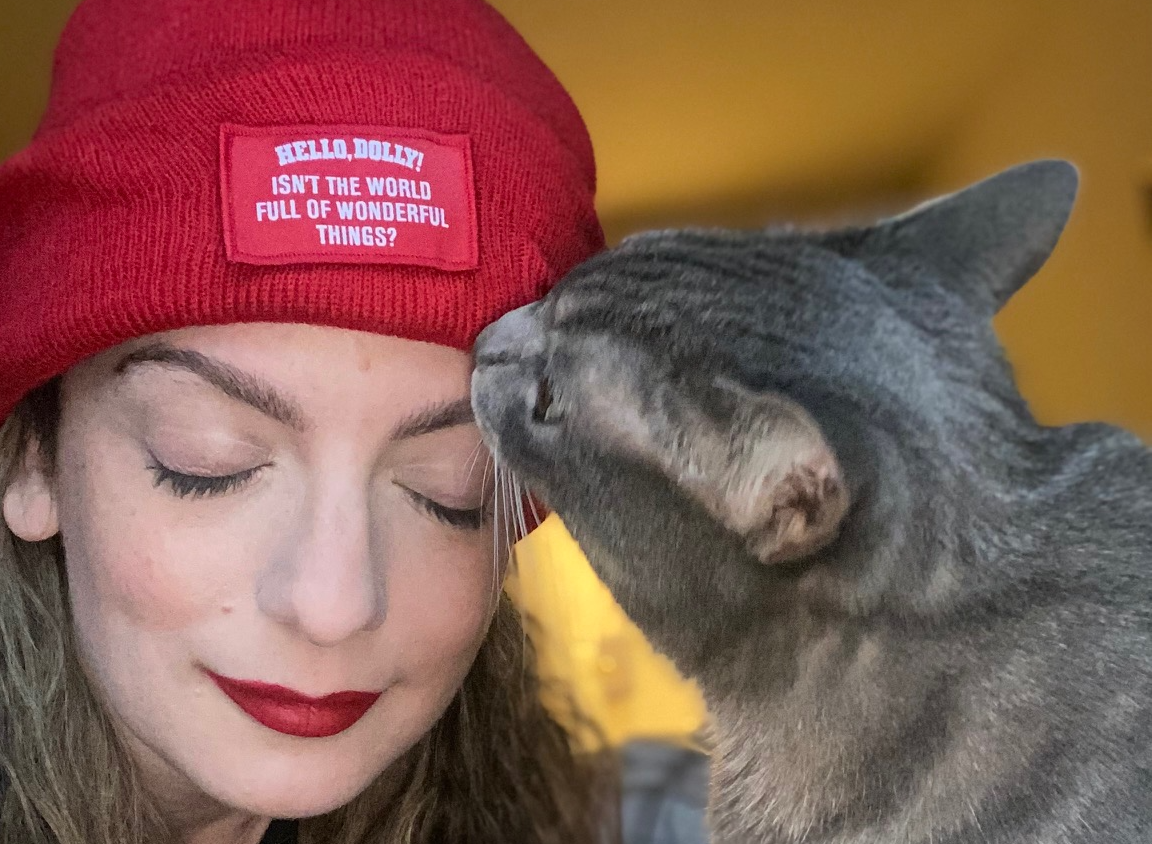 """The author, a woman with dark blonde hair and red lipstick, closes her eyes and wears a red winter knit cap with a label on the front that reads, """"HELLO DOLLY! ISN'T THE WORLD FULL OF WONDERFUL THINGS?"""" as her gray cat, Polly the Demon Queen, sniffs her forehead."""