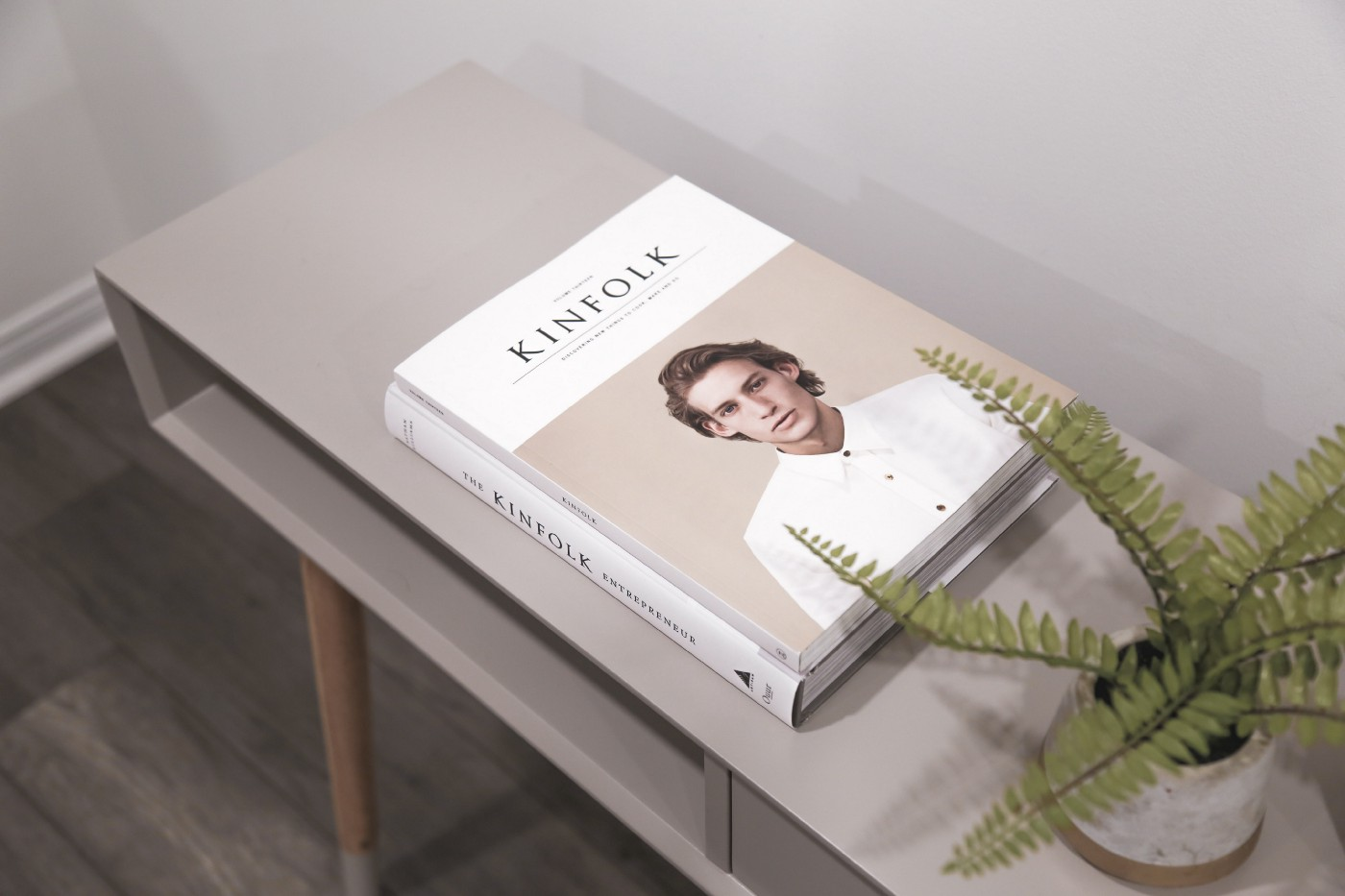 Kinfolk magazine and hardcover book stacked on a grey console table next to a potted fern