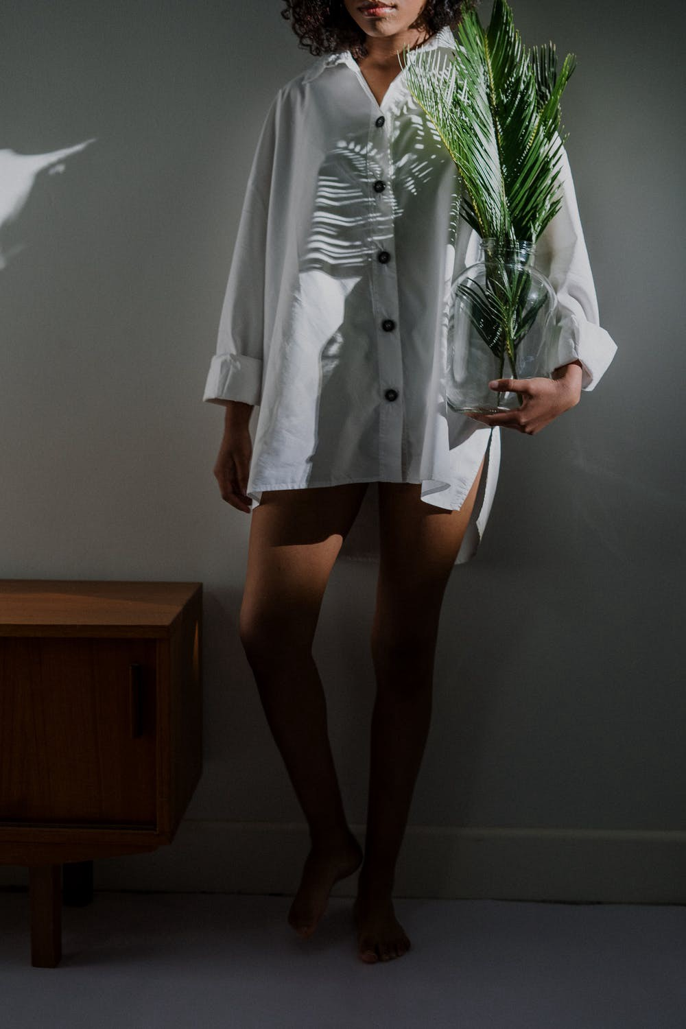 A woman wearing a white button-up coat and carrying a plant vase on her left hand