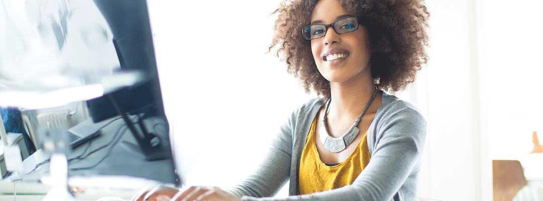Black woman smiling at camera while typing on computer