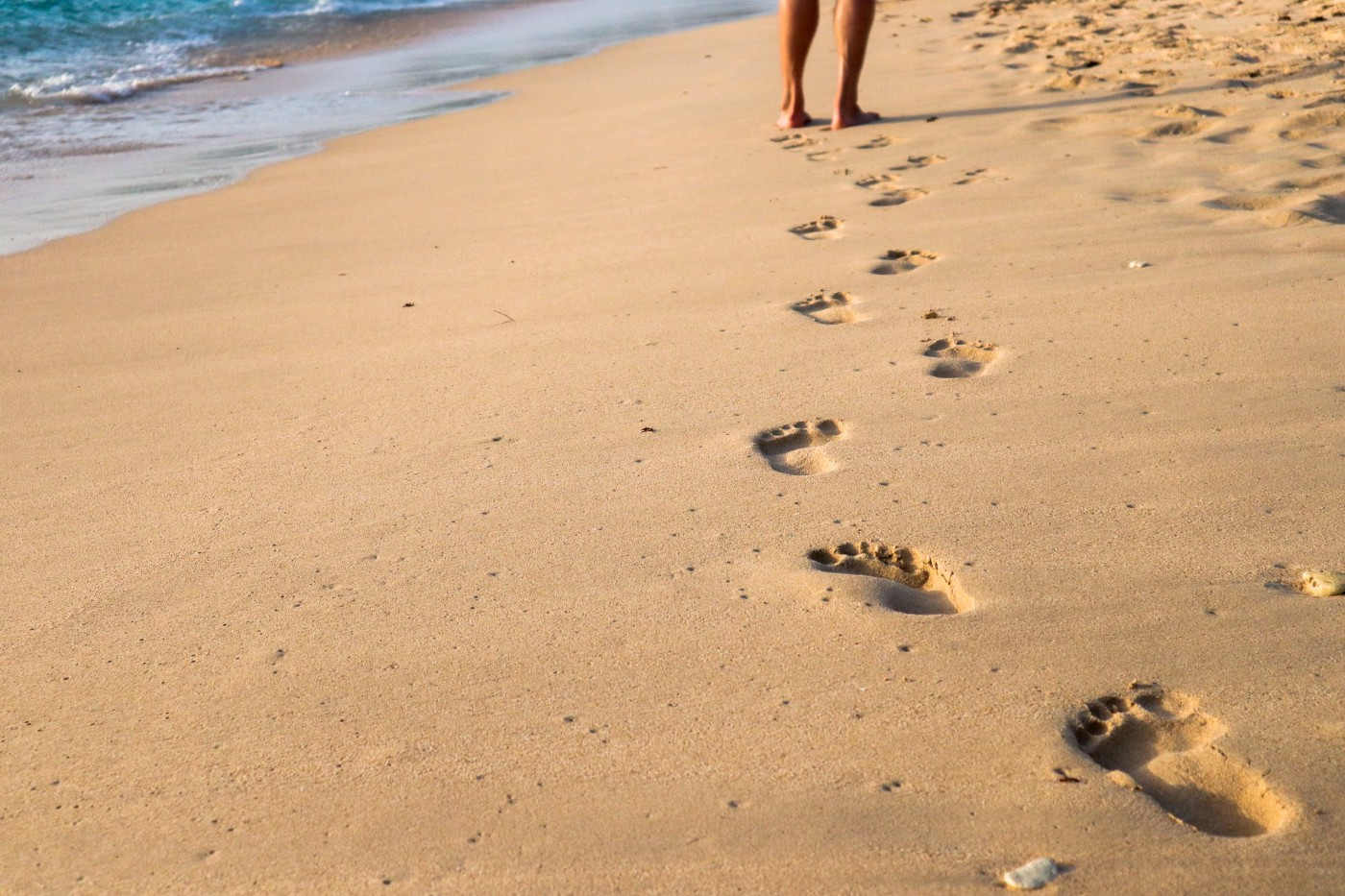 Barefoot footsteps in sand next to water.